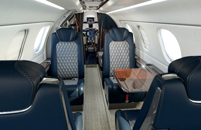 Embraer Phenom 300E interior cabin with blue and gray interior, window shades shut