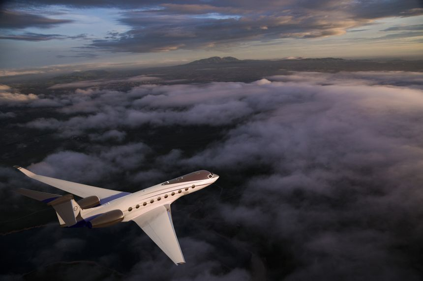 Gulfstream G700 exterior aerial above clouds at sunset rear view